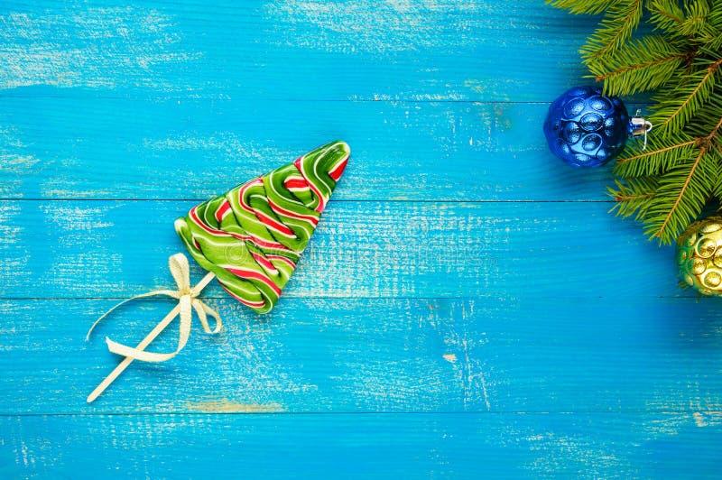 Weihnachtsfestlichkeiten: bunte Lutscher in Form von Fichte auf einem blauen hölzernen Brett stockfotografie