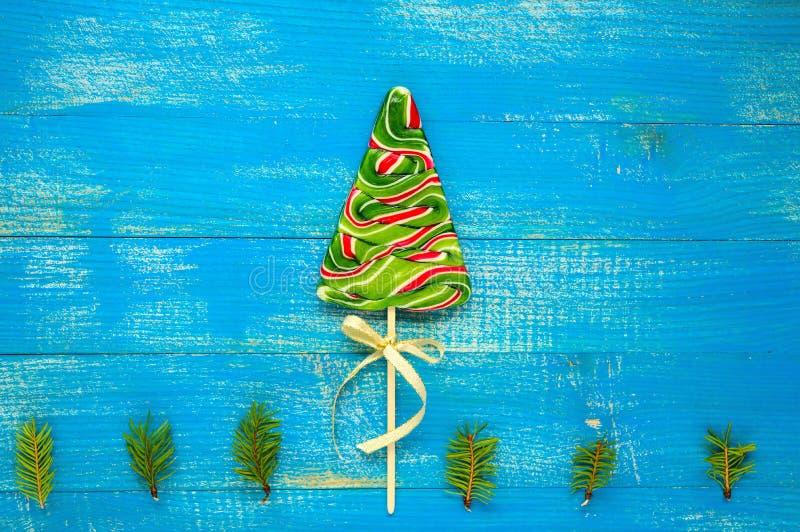 Weihnachtsfestlichkeiten: bunte Lutscher in Form von Fichte auf einem blauen hölzernen Brett lizenzfreies stockfoto