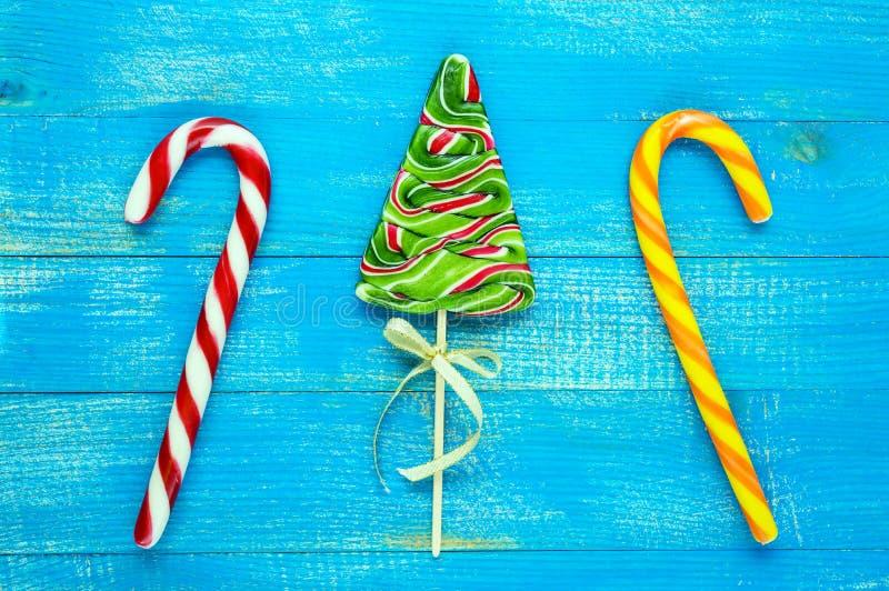 Weihnachtsfestlichkeiten: bunte Lutscher in Form von Fichte, Zuckerstangen auf einem blauen hölzernen Brett stockbild