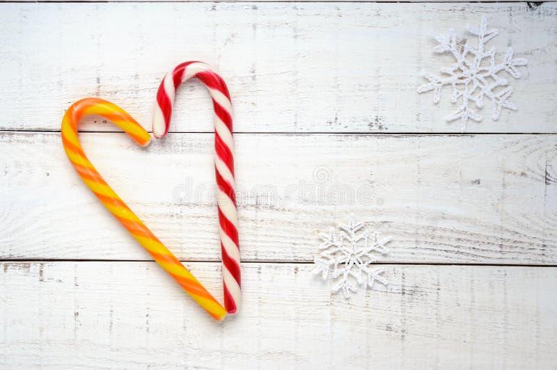 Weihnachtsfestlichkeiten: helle Zuckerstangen, in einer Herzform auf Weiß ein hölzernes Brett Die Draufsicht stockbilder