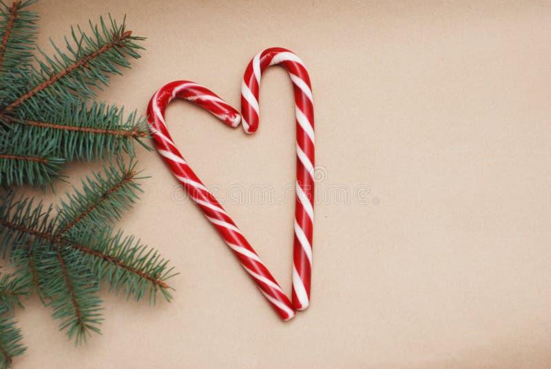 Weihnachtsfestlichkeiten: helle Zuckerstangen, in einer Herzform und in grünen Fichtenzweigen auf Weiß ein hölzernes Brett celebr stockfotografie