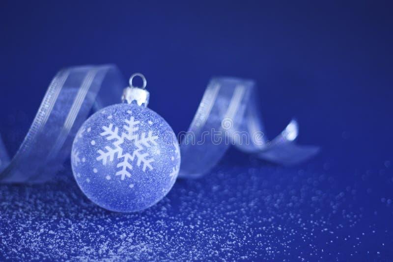 Weihnachtsflitter und -farbband auf Schnee stockfotografie
