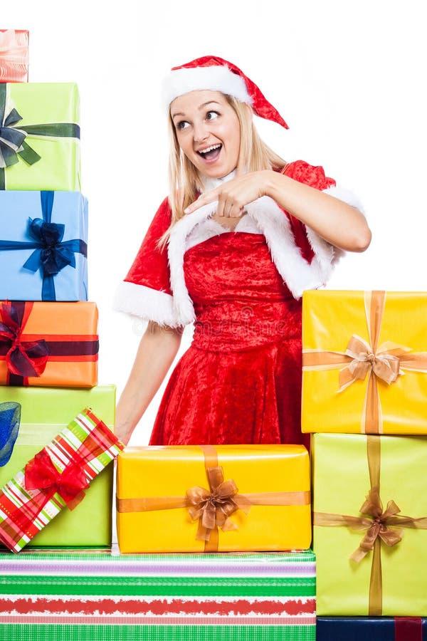 Weihnachtsfrau, die auf Geschenke zeigt stockfoto