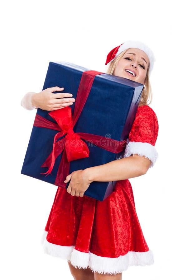 Weihnachtsfrau, die enormes Geschenk trägt stockfotografie