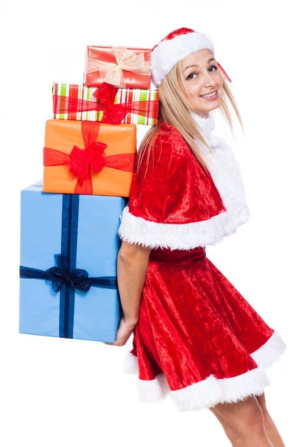 Weihnachtsfrau, die viele Geschenke trägt stockfotografie
