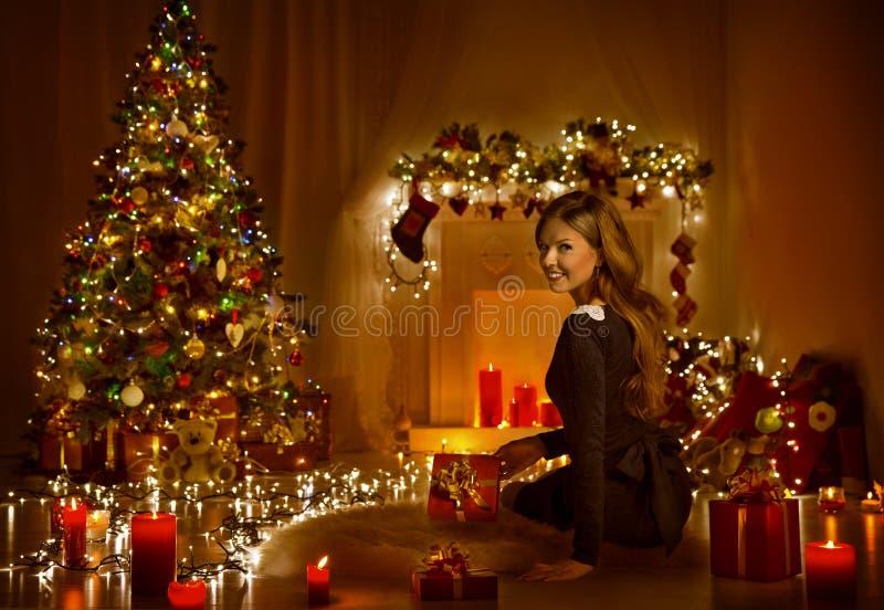 Weihnachtsfrauen-offene anwesende Geschenkbox in Weihnachtsraum, Feiertags-Baum stockbild