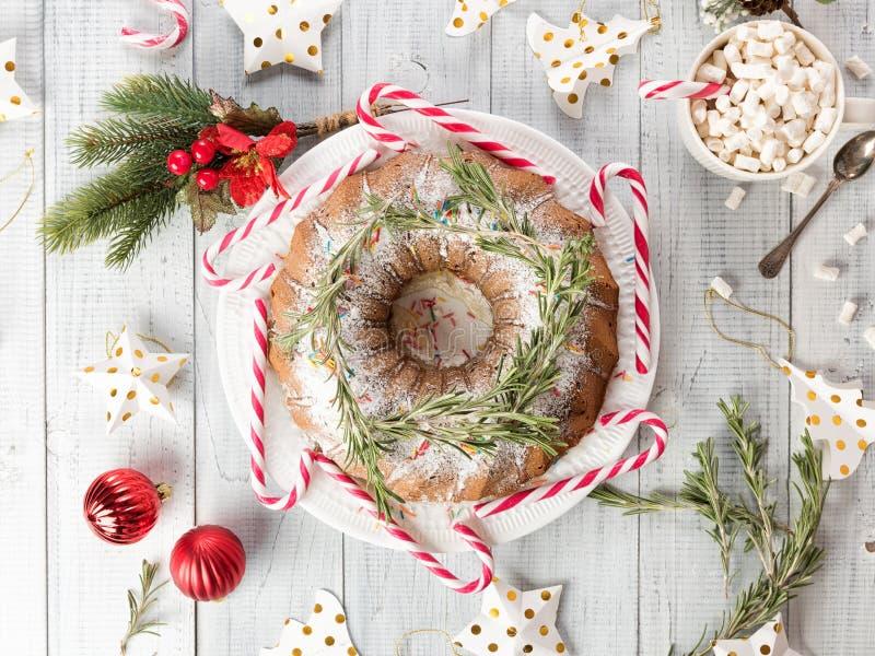Weihnachtsfruchtkuchen auf einem weißen Holztisch Selbst gemachter Pudding mit festlichen Dekorationen, Zuckerstangen lizenzfreie stockfotografie