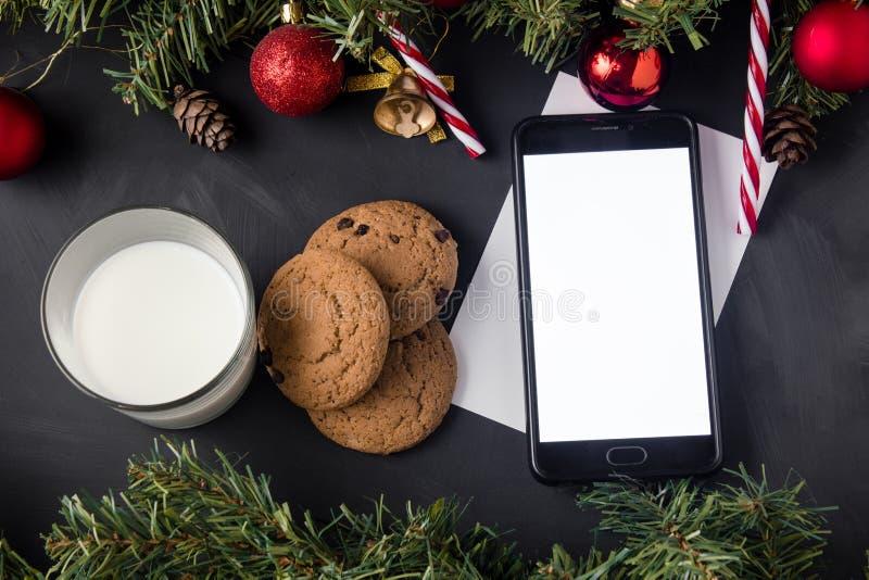 Weihnachtsgarten mit roten Kugeln und goldenen Glocken mit karamellfarbenen Kronen oben und unten auf dem schwarzen Tisch stockfotografie