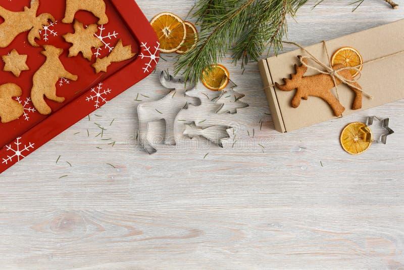 Weihnachtsgebäck, hausgemachte Lebkuchen, Cutter, rotes Backbrett und Geschenkbox auf hellen Holzboden mit Kopie lizenzfreie stockfotos