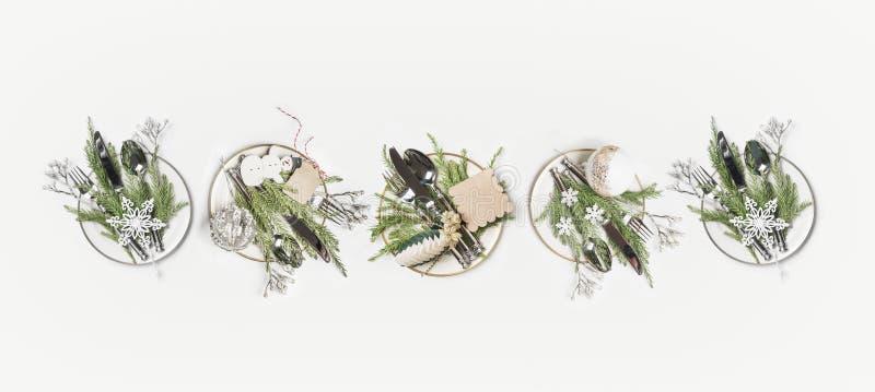 Weihnachtsgedeck-Ebenenlage Reihe von Platten mit Tannenzweigen, Tischbesteck und festlicher Feiertagsdekoration: Schneemann, Sch lizenzfreie stockfotografie