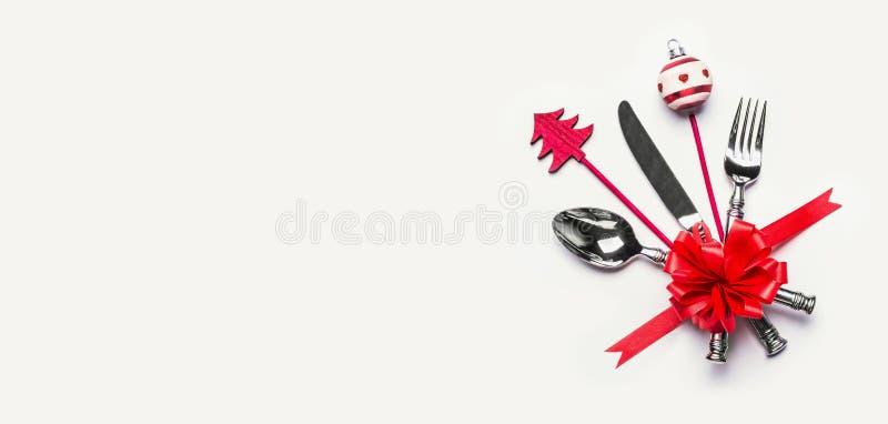 Weihnachtsgedeck mit Tischbesteck, rotem Band und minimaler Dekoration mit Kopienraum auf weißem Schreibtischhintergrund, Draufsi stockfotografie