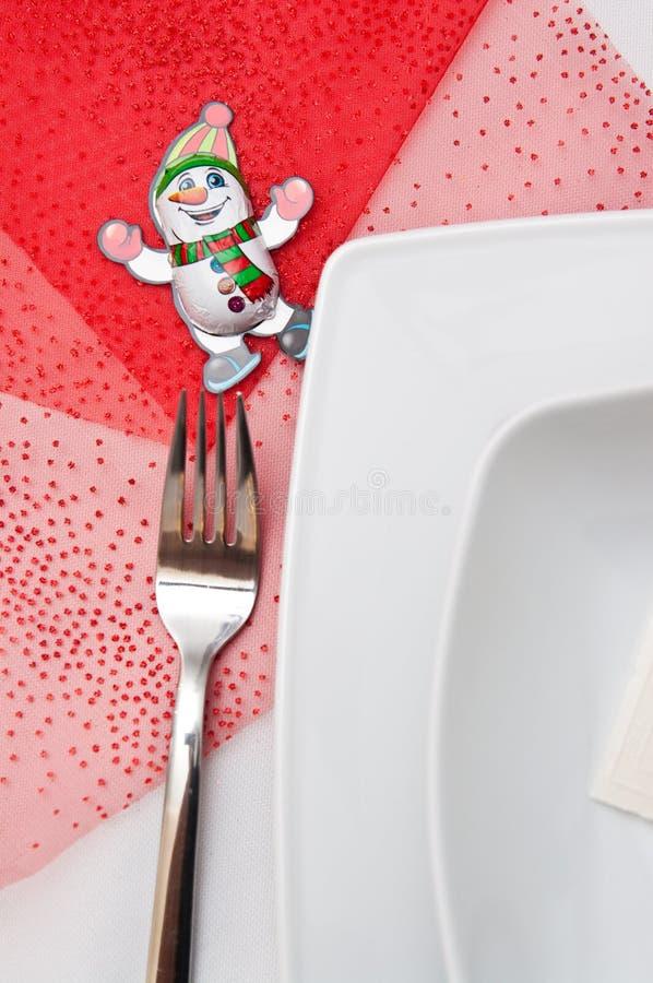 Weihnachtsgedeck mit weißen Platten und roten Dekorationen stockbild