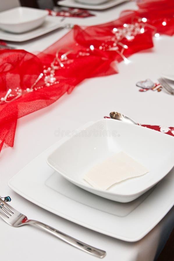 Weihnachtsgedeck mit weißen Platten und roten Dekorationen stockfotos