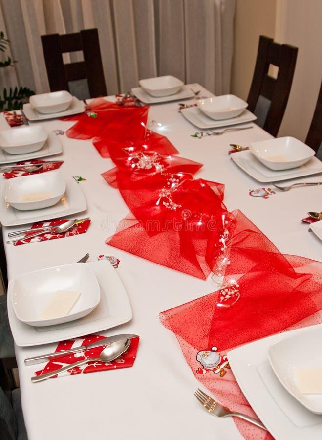 Weihnachtsgedeck mit weißen Platten und roten Dekorationen stockfotografie