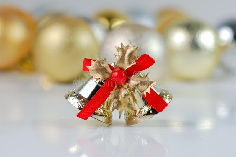 Weihnachtsgelbe und silberne Kugeln und Glocke stockfoto