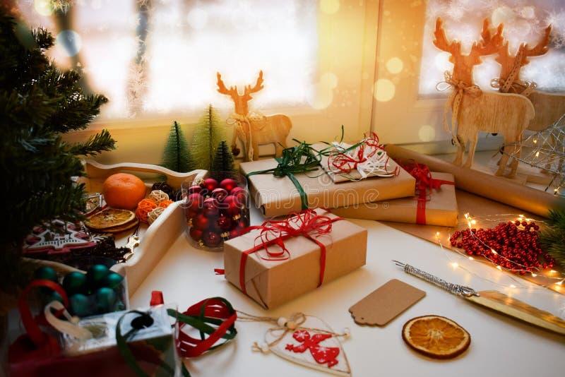 Weihnachtsgemütlicher Plan mit Geschenken im Kraftpapier gebunden mit rotem Band, hölzernes Rotwild, Girlanden, Orangen, Bälle stockfotografie