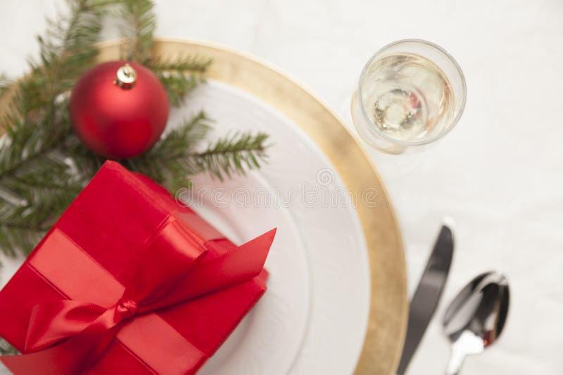 Weihnachtsgeschenk mit festlichem Gedeck am eleganten Speisetische stockfotografie
