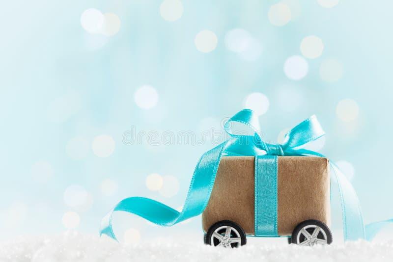 Weihnachtsgeschenk oder -Präsentkarton auf Rädern gegen Türkis bokeh Hintergrund Explosion von Farben und von Formen stockbild