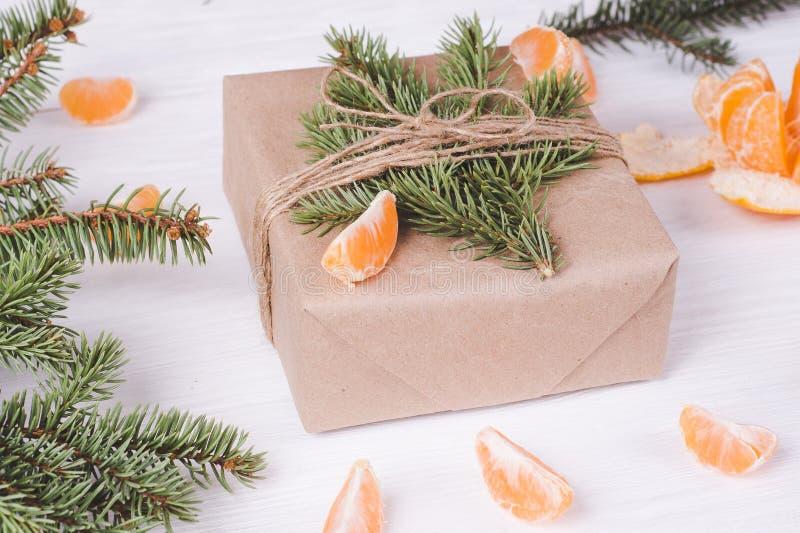Weihnachtsgeschenkbox auf einem wei?en h?lzernen Hintergrund und Tangerinen Der Geist des neuen Jahres stockfotos
