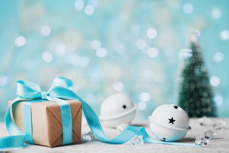Weihnachtsgeschenkbox, Klingelglocke und unscharfer Tannenbaum gegen blauen bokeh Hintergrund Explosion von Farben und von Formen stockfotografie
