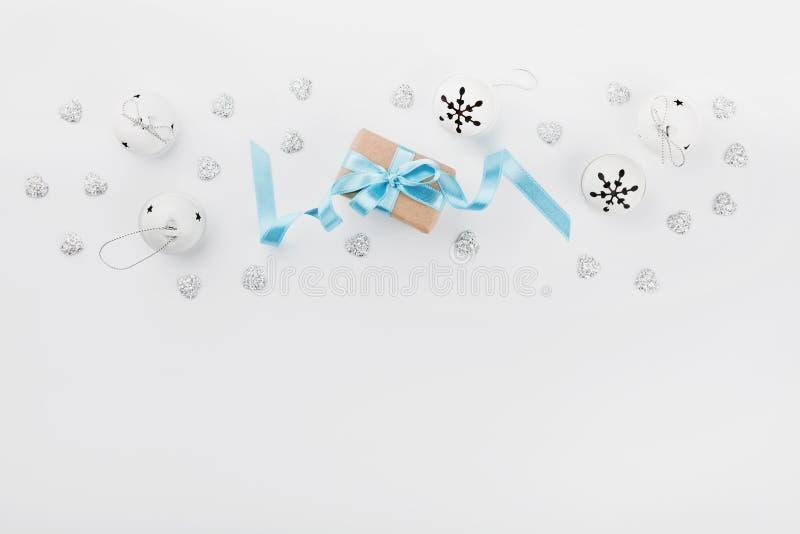 Weihnachtsgeschenkbox mit blauem Band und Klingelglocke auf weißem Hintergrund von oben Explosion von Farben und von Formen Model lizenzfreies stockfoto