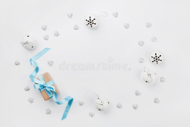 Weihnachtsgeschenkbox mit blauem Band und Klingelglocke auf weißer Tabelle von oben Explosion von Farben und von Formen Modell Fl stockfotografie