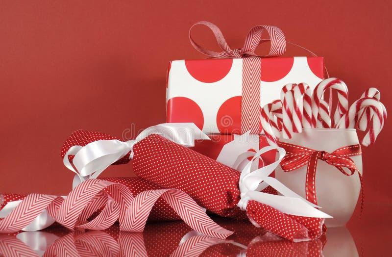 Weihnachtsgeschenkboxen auf rotem Hintergrund, mit StreifenZuckerstangen und Crackern stockfotos