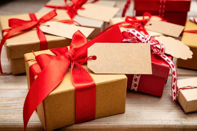 Weihnachtsgeschenkboxen mit leeren Tags auf hölzernem Hintergrund lizenzfreies stockbild