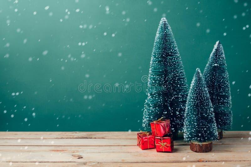 Weihnachtsgeschenkboxen unter Kiefer auf Holztisch über grünem Hintergrund lizenzfreie stockfotos