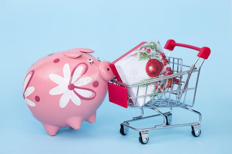 Weihnachtsgeschenke in einer Supermarktlaufkatze auf einem blauen Hintergrund stockfotos