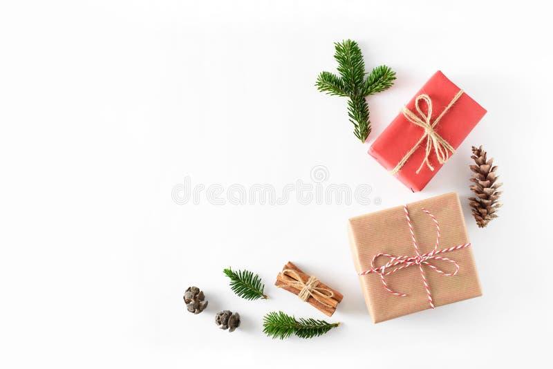 Weihnachtsgeschenke eingewickelt im Handwerk braun und rotes Papier verziert mit Tannenbaum- und Kiefernniederlassungen und Kegel stockbilder
