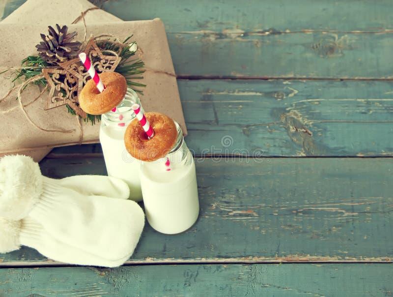 Weihnachtsgeschenke, Handschuhe, Milch in den Flaschen und kleine Schaumgummiringe lizenzfreies stockfoto