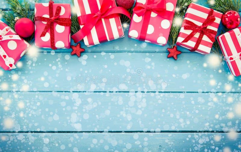 Weihnachtsgeschenke mit Dekoration auf blauem Holztisch stockfotografie