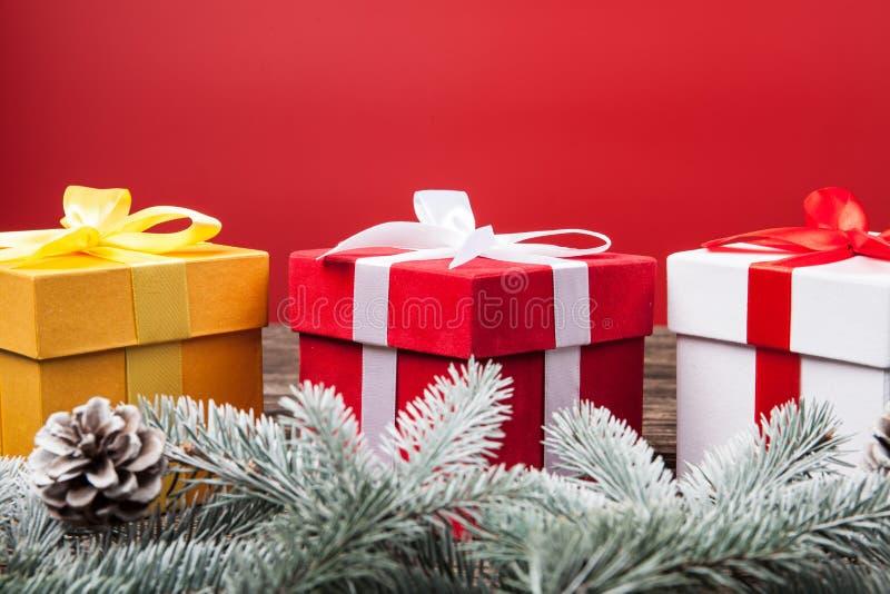 Weihnachtsgeschenkgeschenke auf rotem Hintergrund Weiße und golden und rote Geschenkboxen des Schneetannenbaums mit Bandbögen und lizenzfreie stockbilder