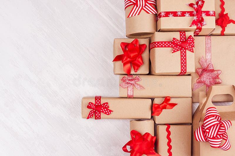 Weihnachtsgeschenkhintergrund - verschiedene Kraftpapiergeschenke mit roten Bändern und Bögen auf weichem hellem weißem hölzernem stockbild