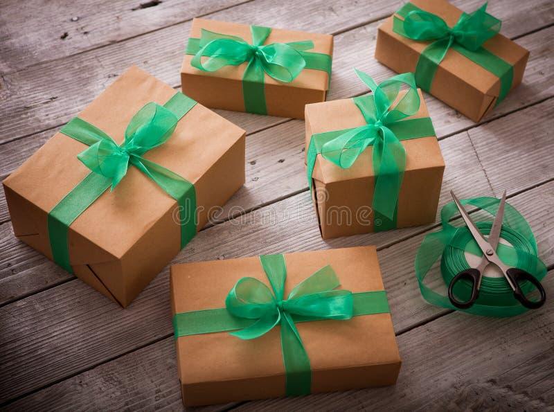 Weihnachtsgeschenkkasten stellt sich mit braunem Papier und grünem Band dar lizenzfreie stockbilder