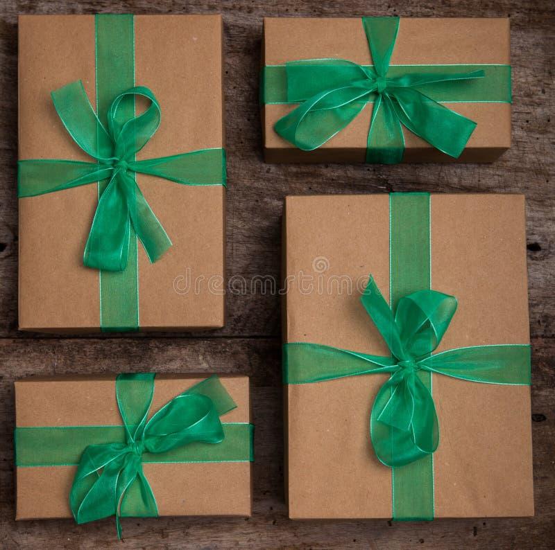 Weihnachtsgeschenkkasten stellt sich mit braunem Papier und grünem Band dar stockfotos