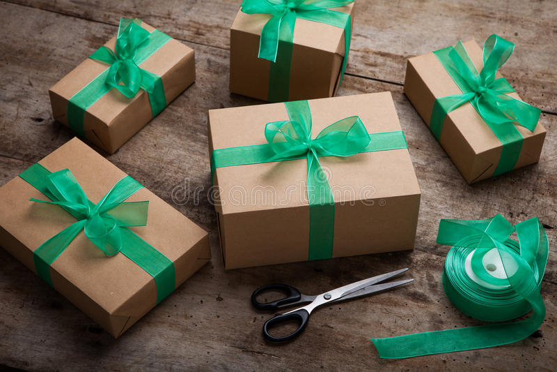Weihnachtsgeschenkkasten stellt sich mit braunem Papier und grünem Band dar stockfotografie