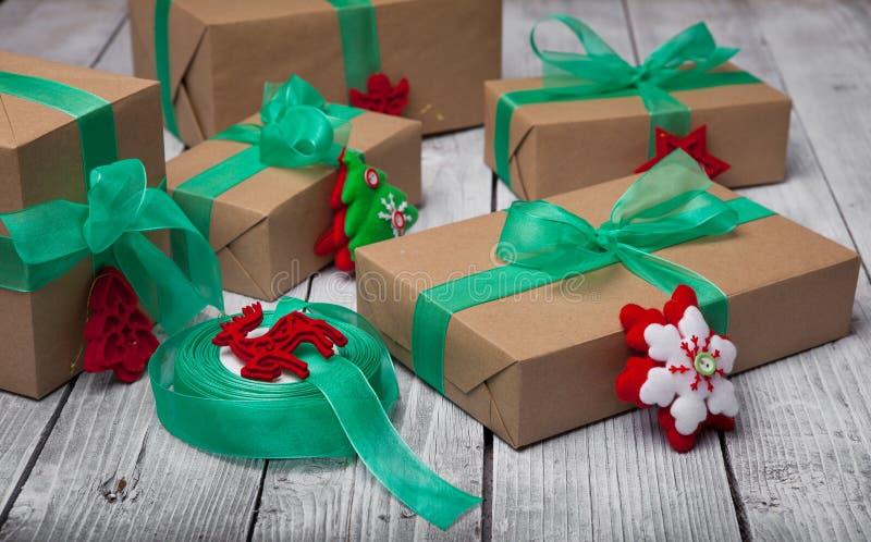Weihnachtsgeschenkkasten stellt sich mit braunem Papier und grünem Band dar stockbilder