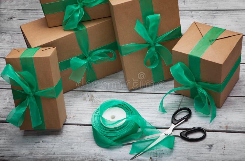 Weihnachtsgeschenkkasten stellt sich mit braunem Papier und grünem Band dar stockfoto
