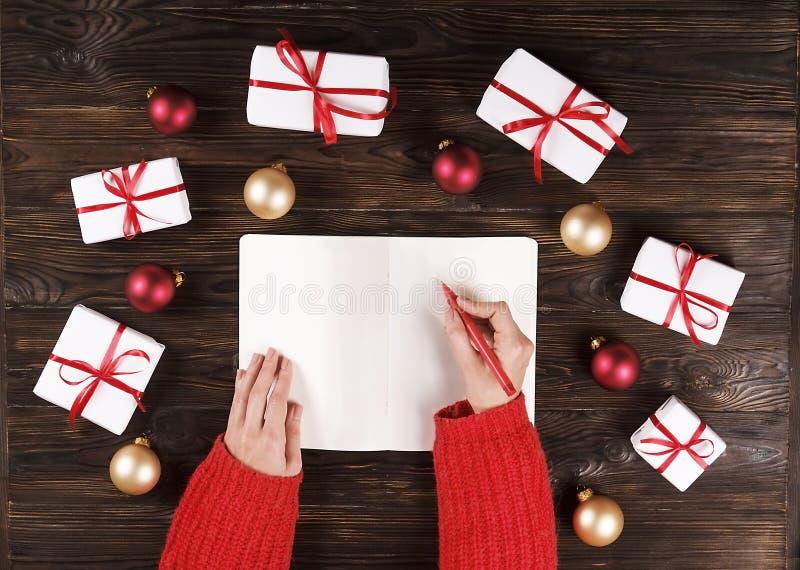 Weihnachtsgeschenkkasten stellt sich mit roten Bällen auf hölzernem Draufsicht-Textraum des Hintergrundes dar lizenzfreie stockfotografie