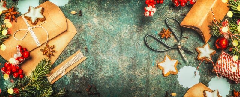Weihnachtsgeschenkverpackung mit kleinen Pappschachteln, Scheren, Feiertagsplätzchen und festlichen Dekorationen auf Weinlesehint stockfotos