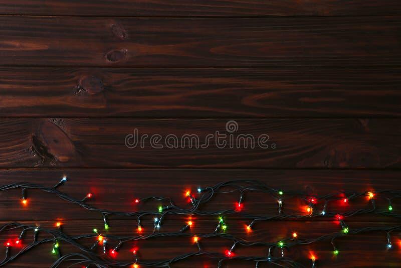 Weihnachtsgirlandenlichter auf braunem Hintergrund, Kopienraum lizenzfreie stockfotos