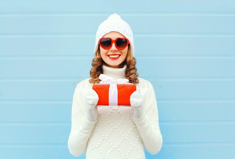 Weihnachtsglückliche lächelnde junge Frau mit Strickmütze-Strickjackensonnenbrille der Geschenkbox tragender über blauem Hintergr lizenzfreie stockbilder