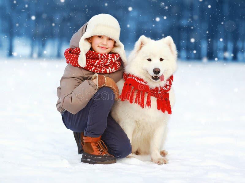 Weihnachtsglücklicher Jugendlichjunge, der mit weißem Samoyedhund am Wintertag, -kind und -hund auf Schnee geht stockfotografie