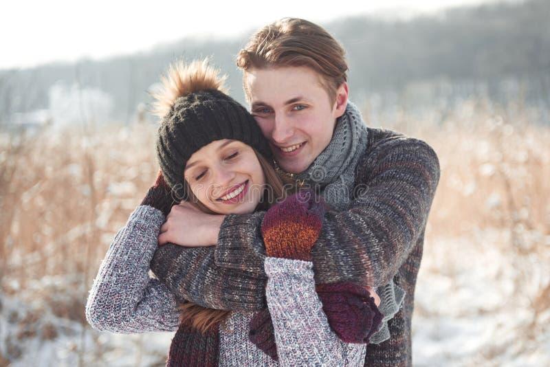 Weihnachtsglückliches paar in der Liebesumarmung im kalten Wald des verschneiten Winters, Kopienraum, Parteifeier des neuen Jahre stockbild