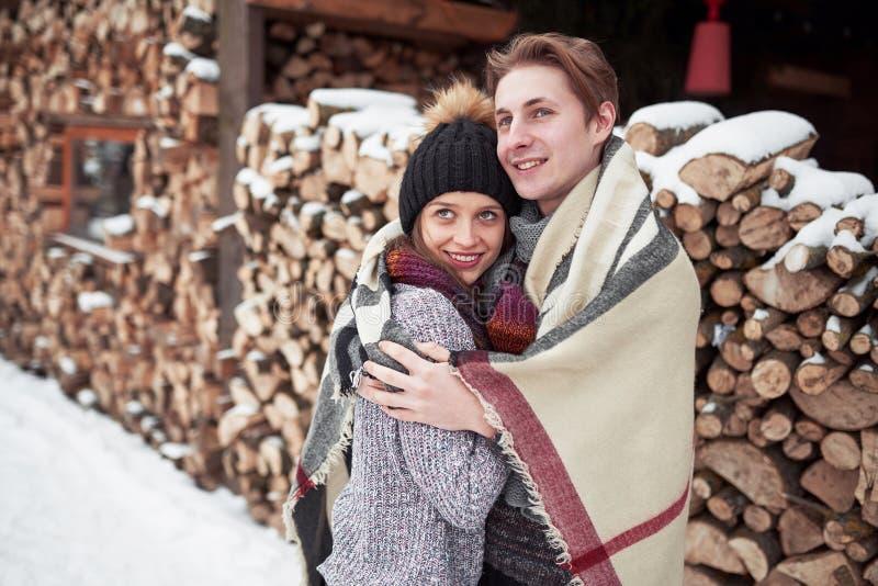 Weihnachtsglückliches paar in der Liebesumarmung im kalten Wald des verschneiten Winters, Kopienraum, Parteifeier des neuen Jahre stockfotos
