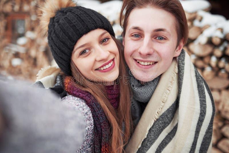 Weihnachtsglückliches paar in der Liebesumarmung im kalten Wald des verschneiten Winters, Kopienraum, Parteifeier des neuen Jahre stockfoto