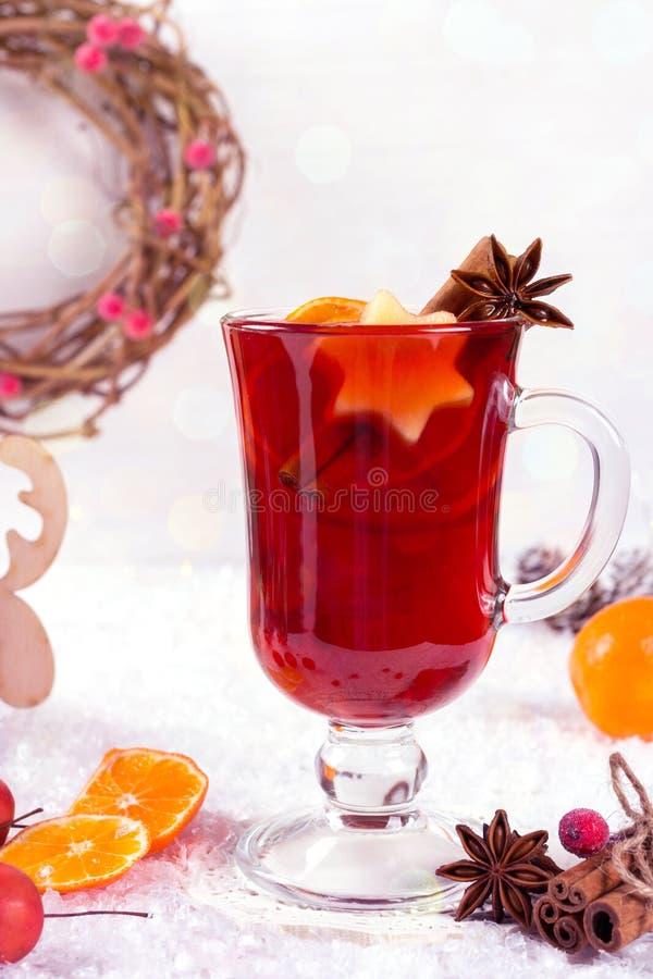Weihnachtsglühwein mit Orangen und Gewürzen auf Schneehintergrund stockbilder