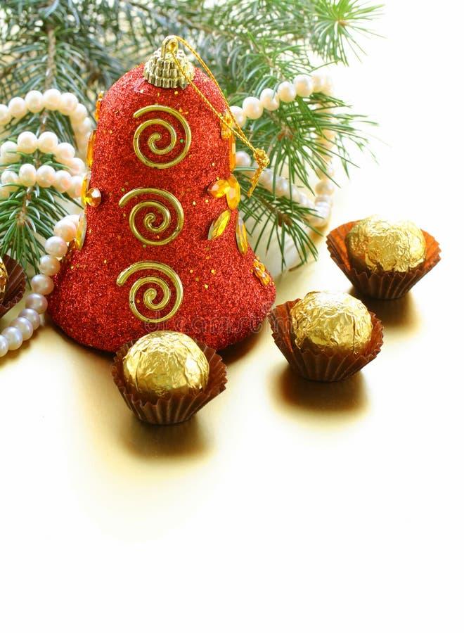 Weihnachtsglocke und -schokoladen stockfoto